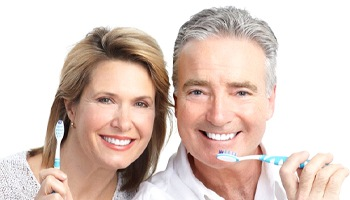 An older couple holding toothbrushes.
