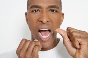 Man flossing teeth with tips from the los angeles dentist Les Latner and the Westside dental Associates team