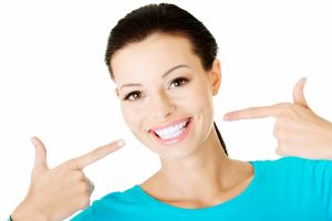 woman pointing at teeth smiling