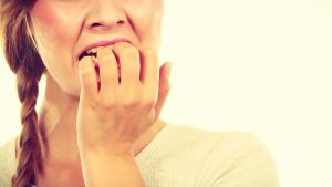 woman biting on four fingernails