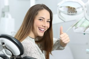 woman in dental chair thumb up