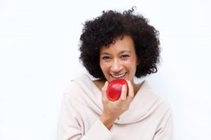 woman biting into a red apple after getting a full-mouth reconstruction in Los Angeles