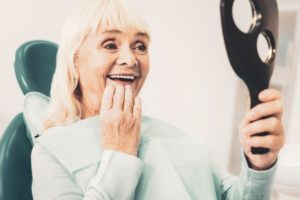 older woman with dental implants in Los Angeles
