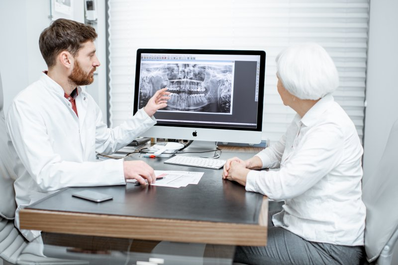 dentist and patient talking during dental implant consultation